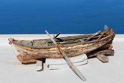 Old wooden rowing boat overlooking Santorini's bay