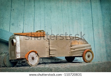 Old wooden rustic toy car on a light blue textured artistic background