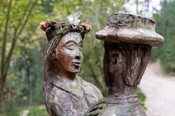 old wooden sculpture in the forest, a man and a woman dancing.Witch Hill park, Lithuania.