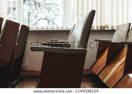 old wooden seats with reclining seats in the event hall of a small provincial town #1549038524