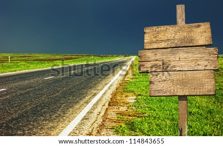 old wooden sign at the country road