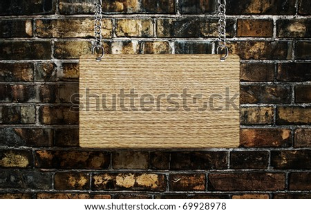 old wooden sign on a chain on the background of a brick wall