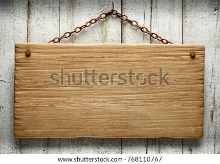 old wooden signboard hanging on an aged wall with a rusty chain