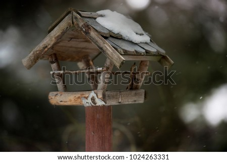 Old wooden snow covered birdhouse in the wintry garden. #1024263331