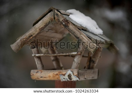 Old wooden snow covered birdhouse in the wintry garden. #1024263334