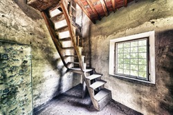Old wooden stairs in abandoned home with window.