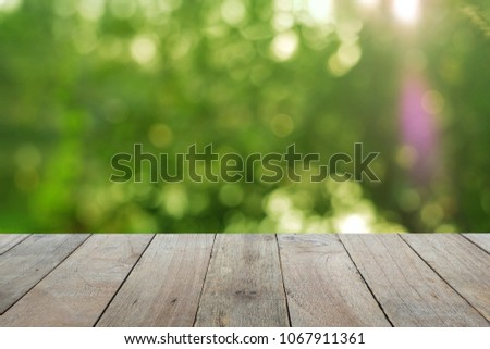 Shutterstock Old wooden table foreground with blurred green bokeh background, empty space Place a product. Nature and health concept.