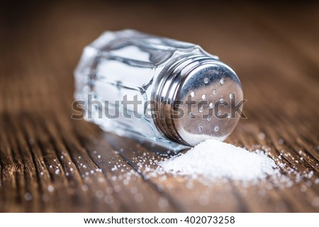 Old wooden table with a Salt Shaker (close-up shot; selective focus)
