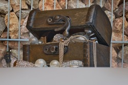 old wooden treasure chest behind a lattice stone wall full of jewelry is guarded by a police officer as a miniature figure