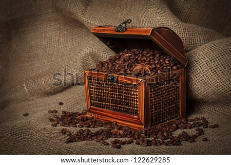Old wooden treasure chest filled with coffee beans and anise stars . Focused on chests corner.