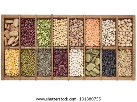 old wooden typesetter box with 16 samples of assorted legumes: green, red and French lentils, soybean, green and yellow pea, fava bean, kidney, black, mung chickpea bean,adzuki bean