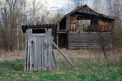 Old wooden village shabby lavatory on the foreground with an abandoned broken house on the background at countryside in springtime. Poverty in the russian village