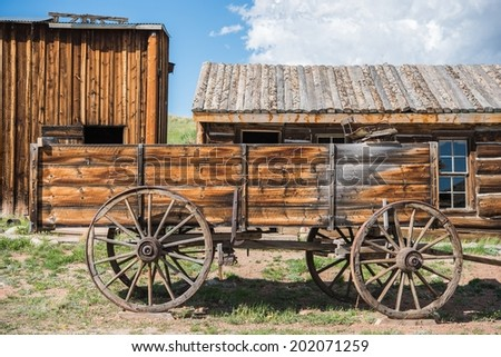 Old Wooden Wagon and Aged Log Cabins