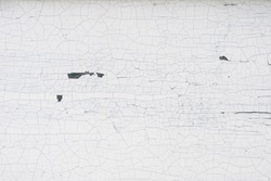 Old wooden wall with cracked and peeling white paint. Textured background.