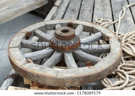 Old wooden wheel lying on a wooden cart #1178089579