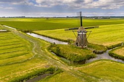 Old wooden windmill in green agricultural grassland. Friesland, the Netherlands.