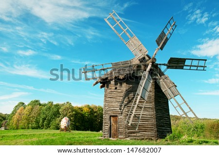 Old wooden windmill in the background of the autumn forest