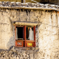 Old wooden window with broken glass in small asian village