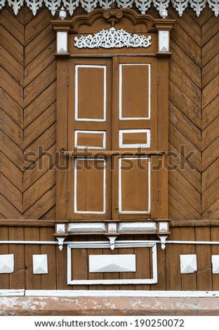 Old wooden window with carved wooden ornaments. Closed window in a village house.