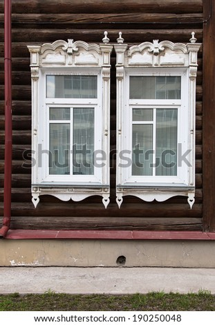 Old wooden window with carved wooden ornaments. Open window in a village house.
