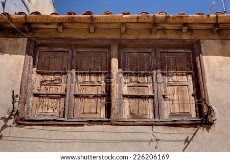 Old wooden window with rain gutter and clothes dryer