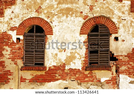 Old wooden windows in a grunge brick wall