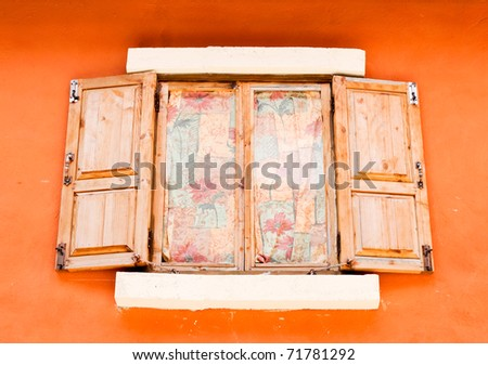 Old wooden windows on the orange wall of country house. - stock photo