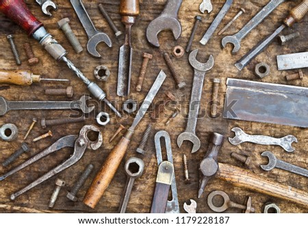 Old woodwork and engineering tools on grungy rag background with nuts, bolts and screws.