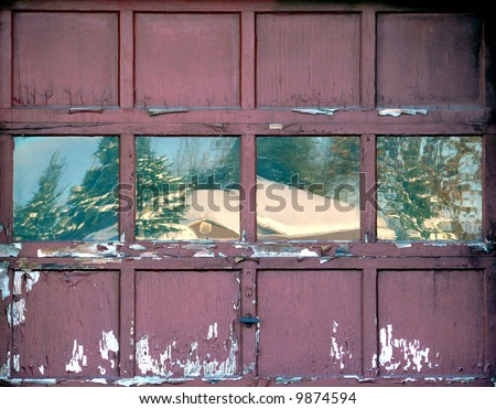 Old workshop door with a winter scene reflecting in the windows