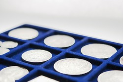 Old world numismatics coin collection on blue tray isolated white background