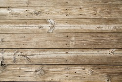 Old, worn and sandy beach planks on a boardwalk