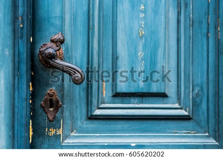 Old worn blue painted entrance door with black wrought iron latch close up image as background