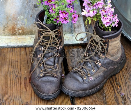 Old worn boots with flowers planted in them on a wooden deck