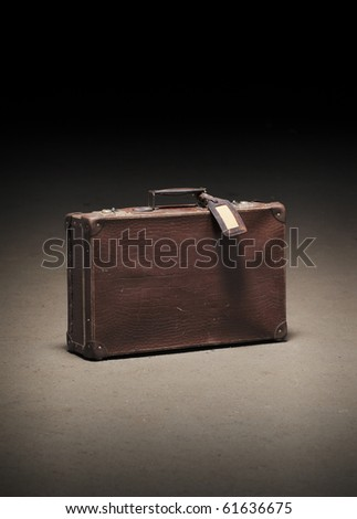 Old worn brown suitcase on dirty concrete floor