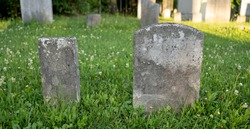 Old worn grave markers in cemetery