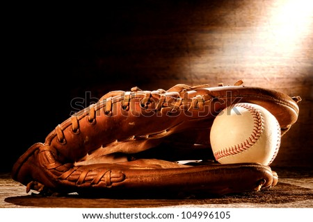 Old worn leather baseball catcher sport glove and aged stitched ball on antique wood boards in soft nostalgic Americana light