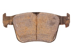 Old worn out and worn out brake pad on a white background, close-up, isolate. Concept of performance and composition of friction linings
