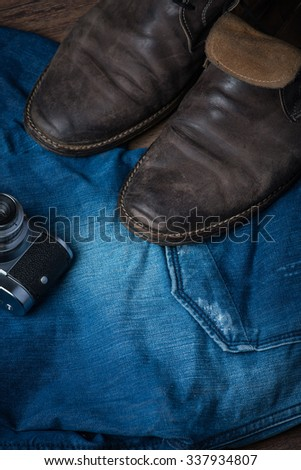 Old worn out brown leather shoes with camera and jeans on the wooden floor #337934807