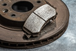 Old worn out car brake disc and brake pads, macro shot close-up