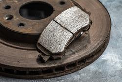 Old worn out car brake disc and brake pads, macro shot close-up