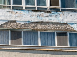Old worn out communist apartment building with cracked peeling paint.
