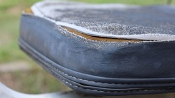 Old worn out leather seats. Weathered and damaged black leather upholstery with sponge inside. Closely selected focus.