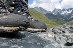 Old worn out trekking boots on the background of alpine landscape. Altai, Russia.