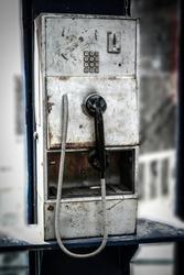 Old worn public phone in telephone box, souvenir of the communism era in Poland