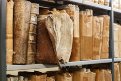 Old worn 17th century books on a shelf in the library's archives