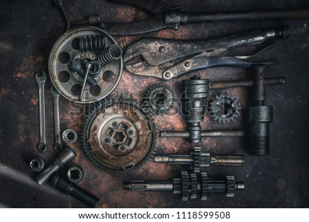 old wrench and tools and Engine spare partsr on rusty background .  motorcycle tools and maintenance equipment and repair