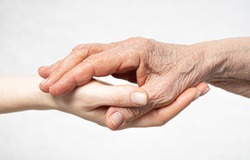 Old wrinkled hand lies on the young hand. Care for old people concept.