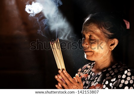 Old wrinkled traditional Asian woman praying with incense sticks inside a temple low light with smoke and beautiful natural sunlight Myanmar