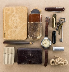 Old wrist watch,notebook,keys,tin spoon,a lighter and other miscellaneous items