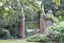 Old wrought iron gates mounted between two tall slim brick gate posts in an English country garden.